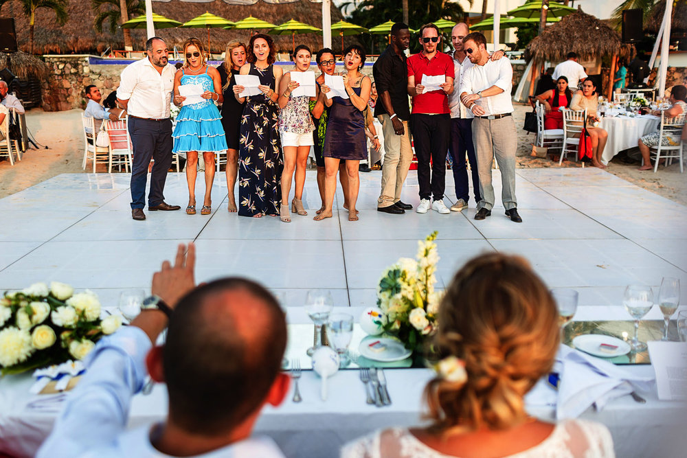Friends of the bride singing a french song to the couple during the speeches