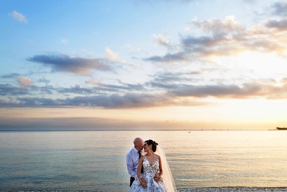 Retrato de pareja en el día de su boda en la playa con el océano pacifico mexicano en el fondo