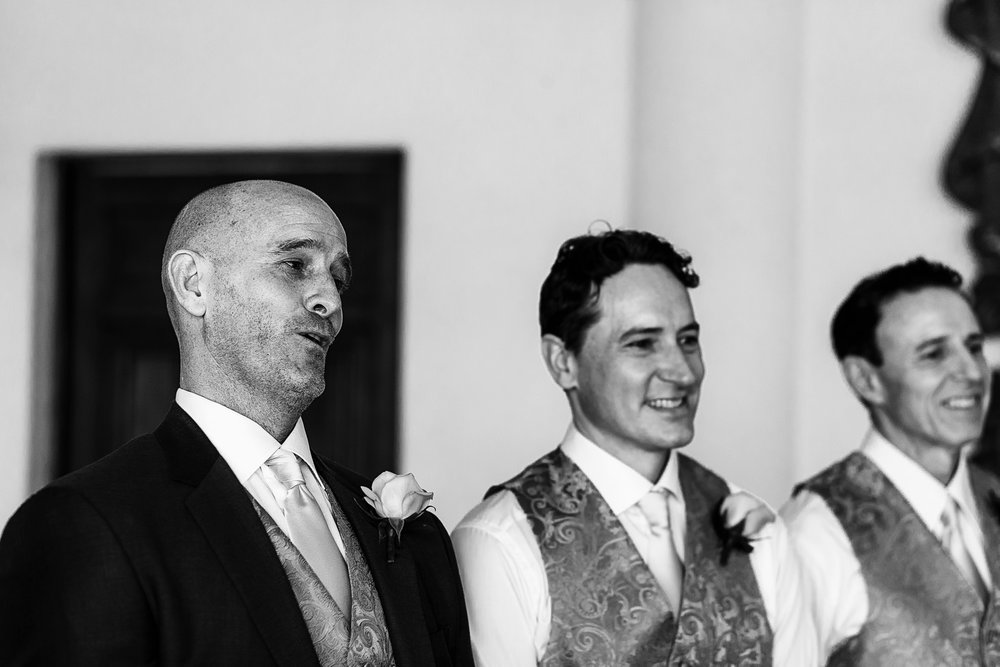 The groom is blown away by the beauty of the bride walking down the aisle
