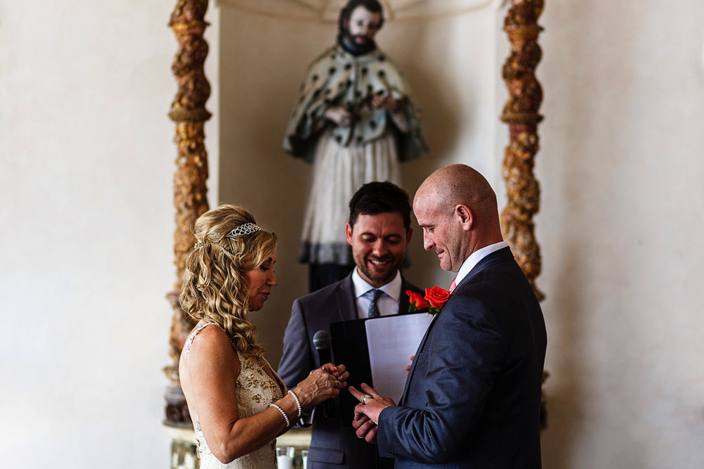 The groom and bride exchange rings during their destination wedding ceremony