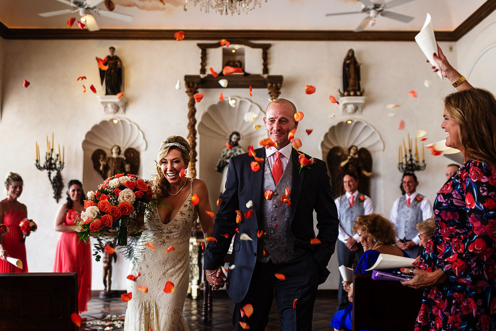 Bride and groom exit from the ceremony as rose petals rain upon them