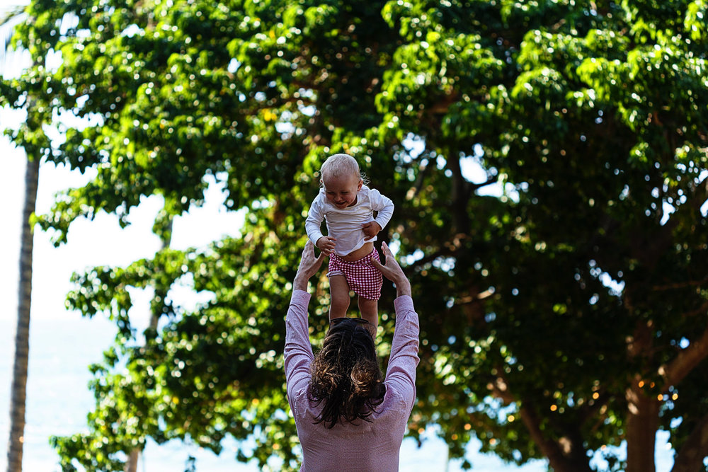 Baby is tossed in the air by her dad