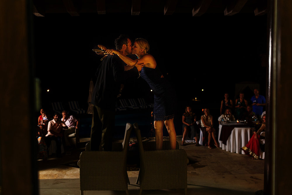Bride and groom kissing up on the chairs