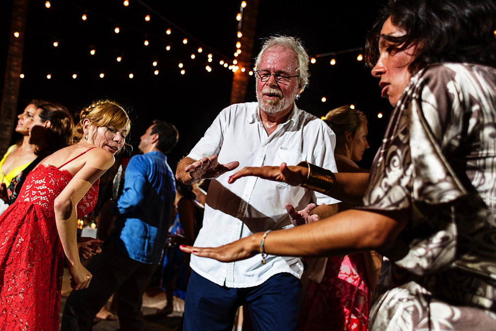 Father of the bride dancing with other wedding guests