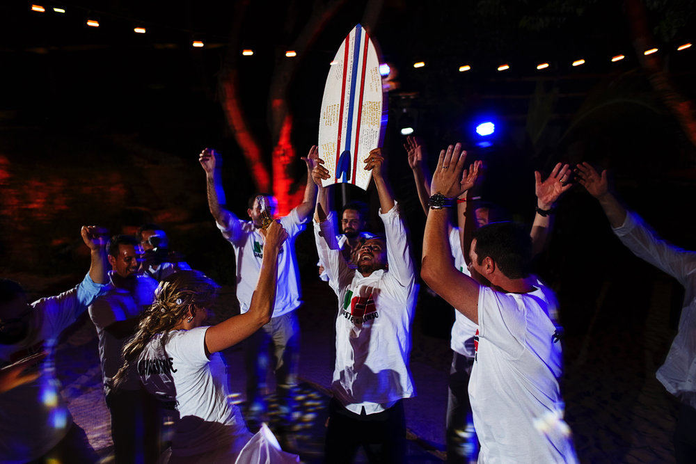 Groom raises a signed surf board as everybody jumps around the happy couple