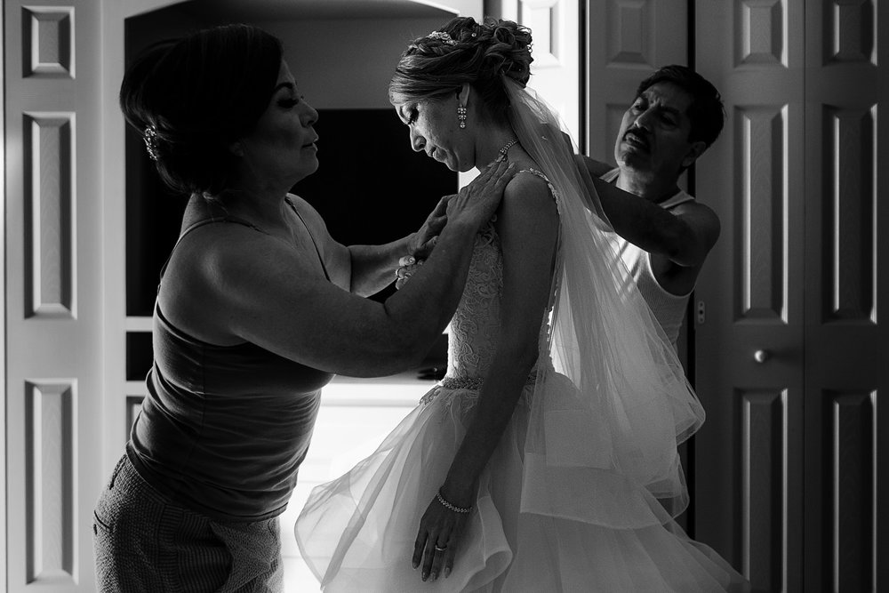 Mom and dad helping their daughter bride to get dress