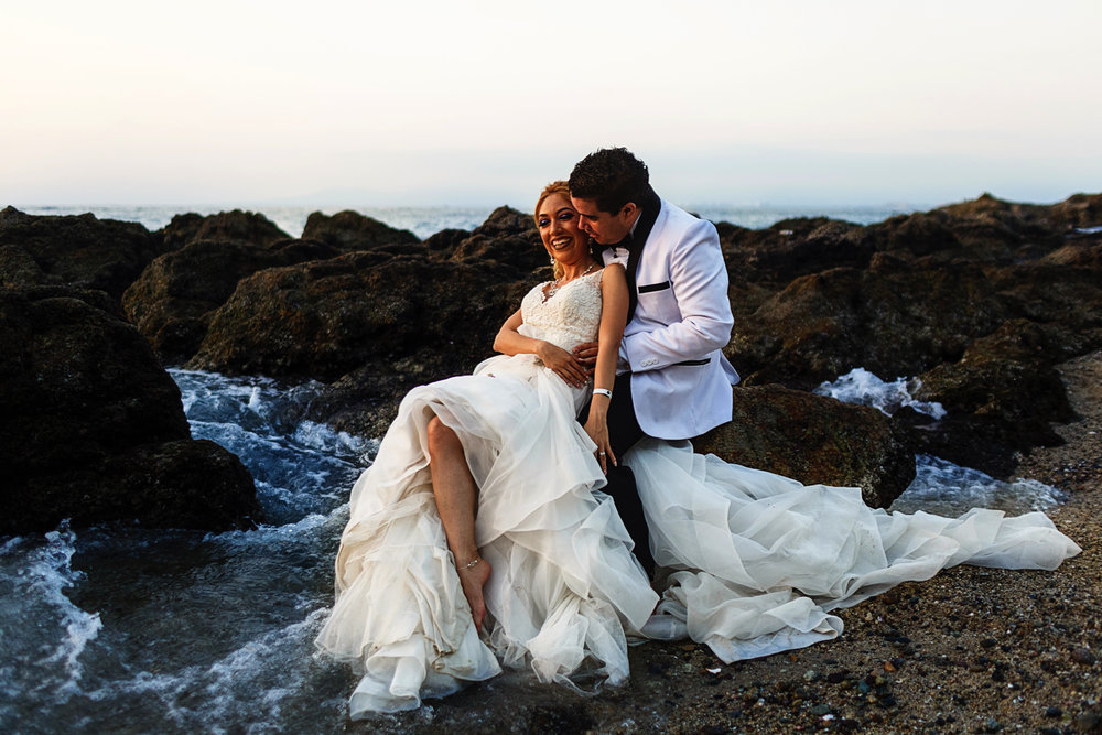 Groom and bride sitting on a rock and getting their feet wet on the pacific ocean in Puerto Vallarta