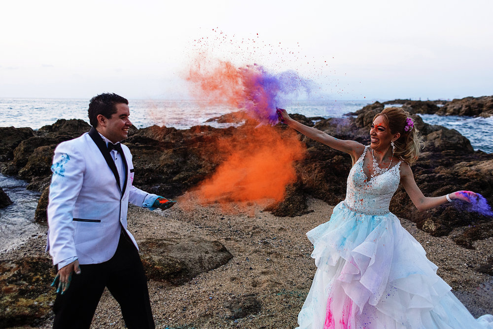 Groom and bride throw colorful holy powder to each other