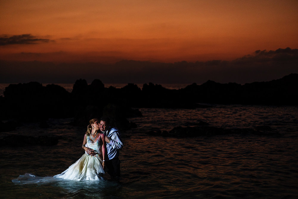 Bride and groom standing inside the pacific ocean under the sunset in Puerto Vallarta