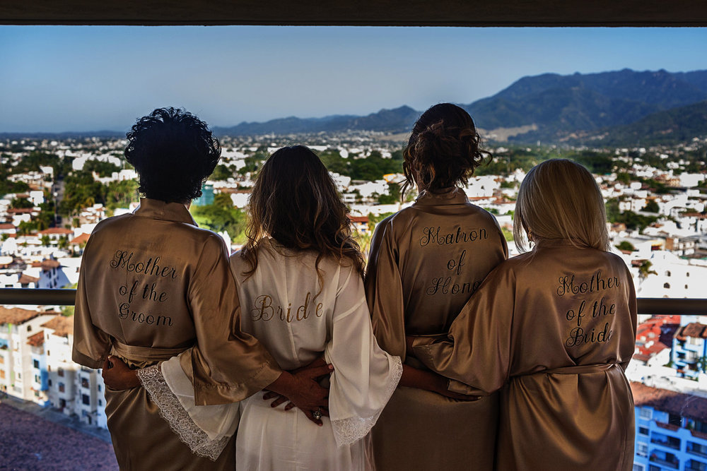 Mothers, matron of honor and bride showing their ropes against a view of Puerto Vallarta