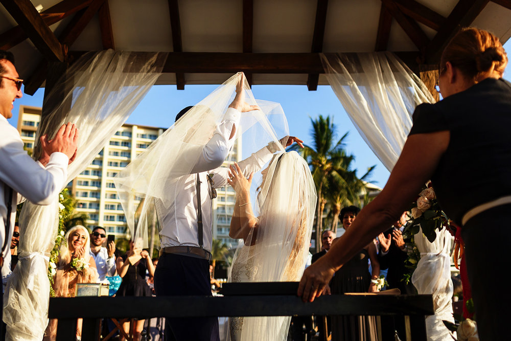 Groom lifts the bride's veil for the kiss at the end of the ceremony