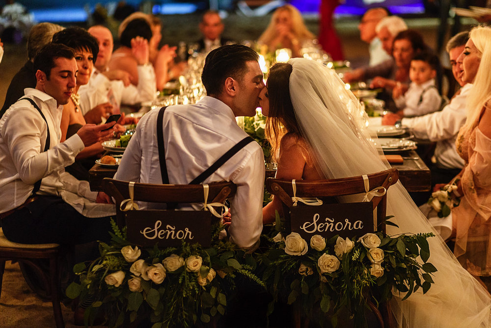 "Bride and groom kiss while sitting at their chairs with hanging signs with words ""Señor"" and ""Señora"""