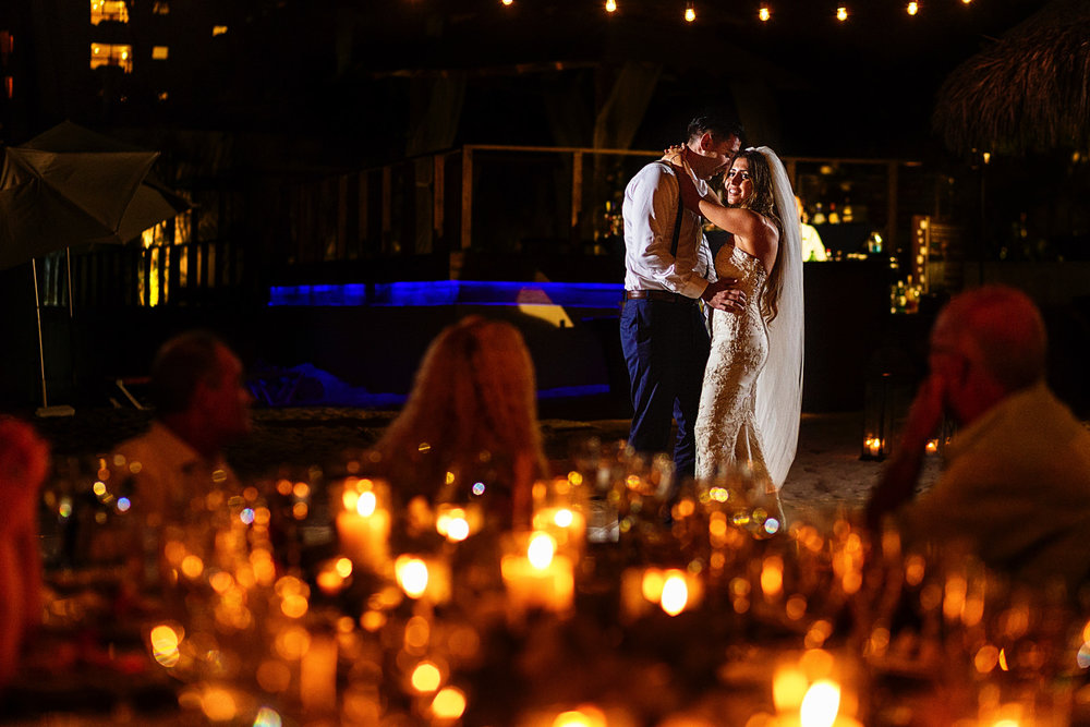 Bride and groom first dance through candles on the table