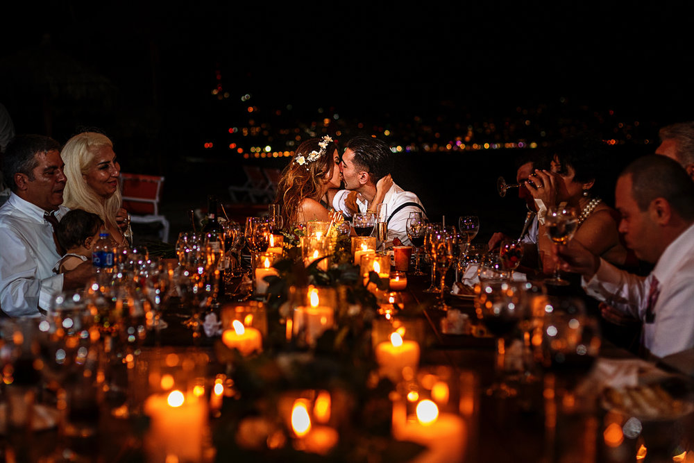 Bride and groom kiss at the end of a long table filled with candles