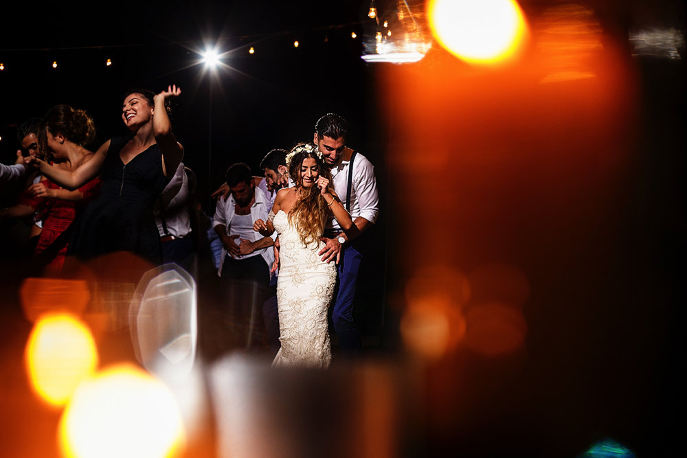 A view of the wedding party through candles, groom and bride dancing in the middle