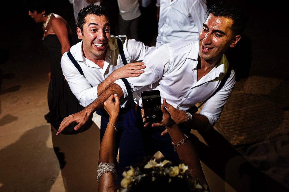 Bride captures a video with her cell phone of the groom and best-man dancing right in front of her