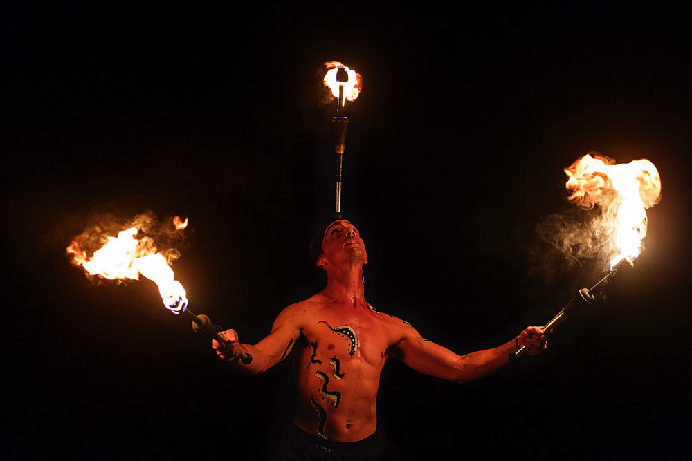 Fire dancer holding a fire stick on his forehead