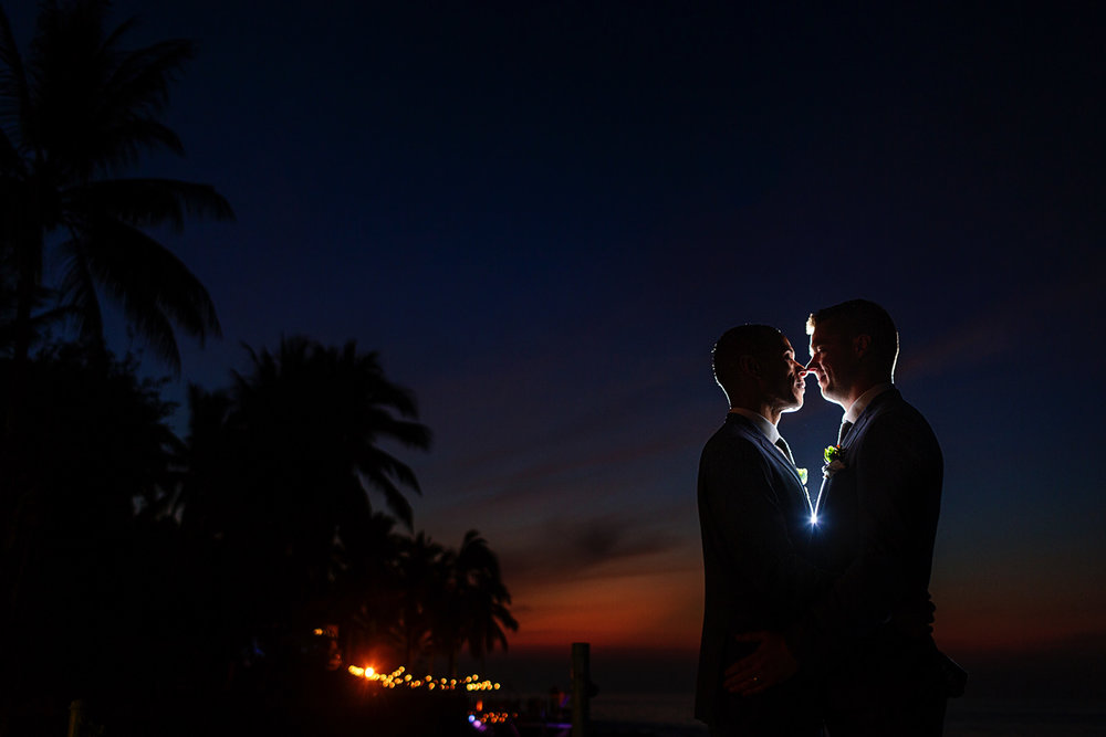 Grooms kissing at sunset after wedding ceremony in Mexico