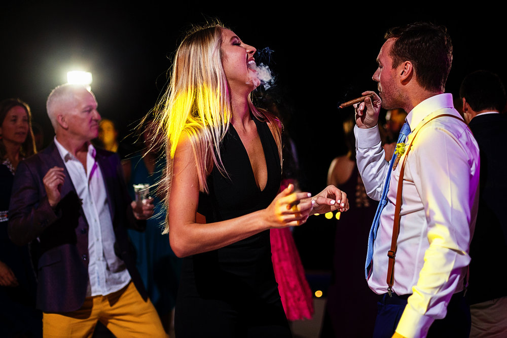 Wedding guests enjoy a cigar in the dancefloor as they dance