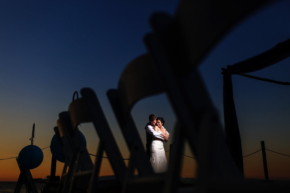 Married couple of groom and bride through the chairs with a magnificent sunset in the background.