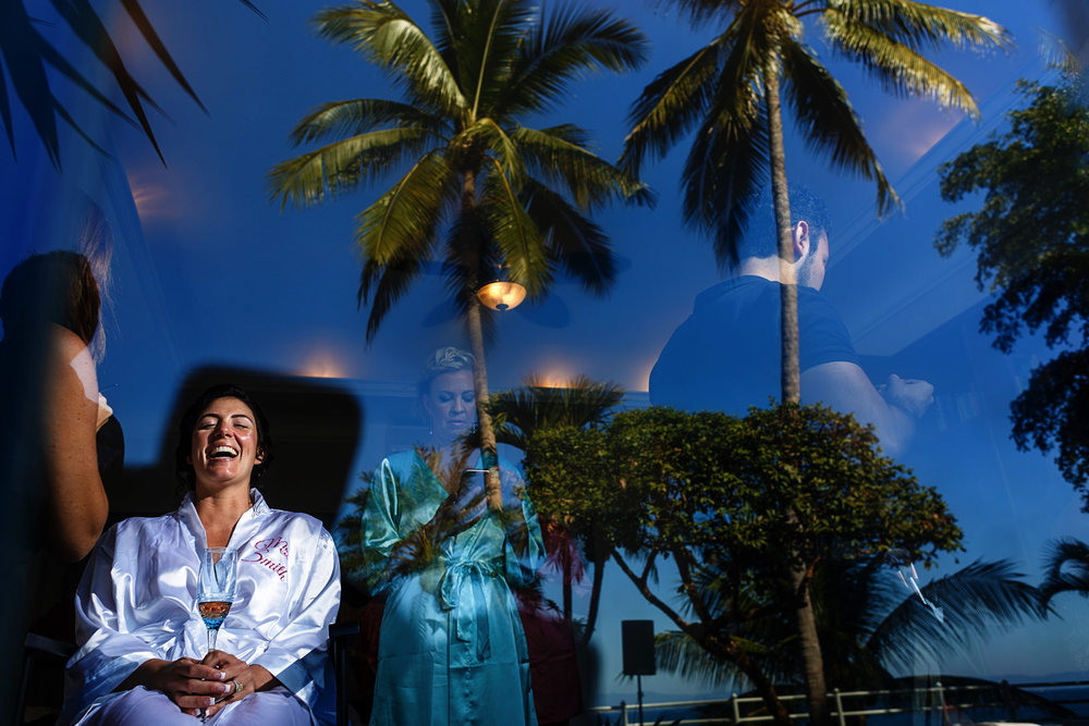 Bride laughing while she is having her make-up, through a window that also reflects the blue sky and palm trees