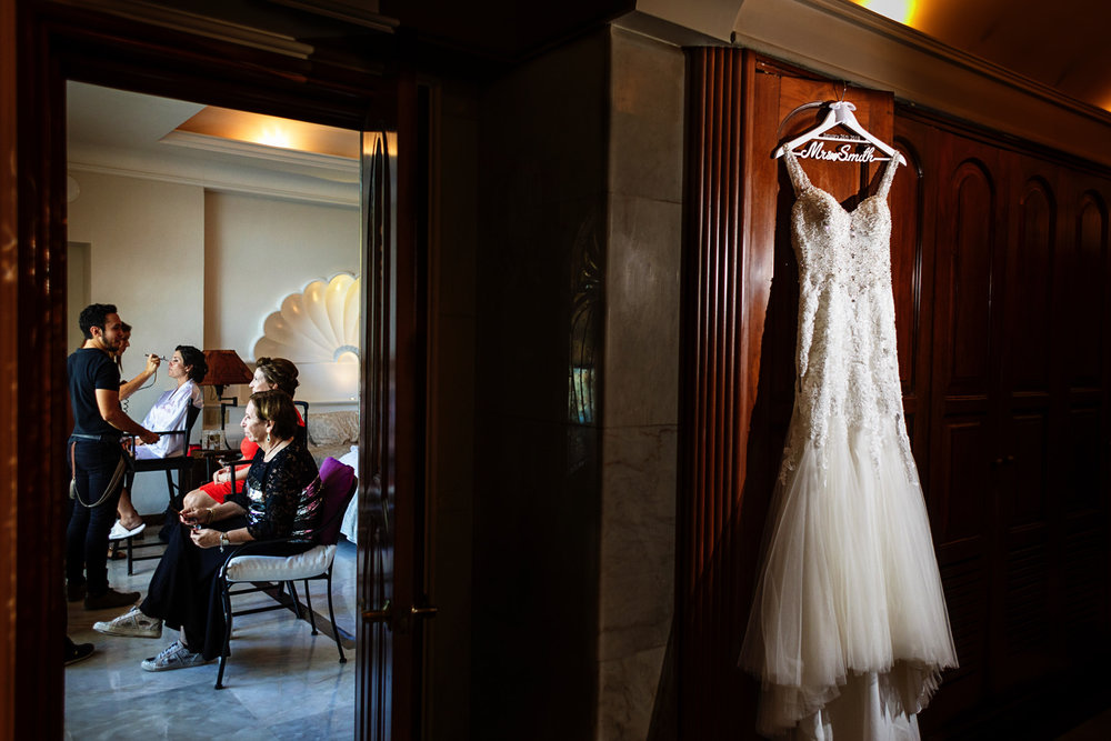 Wedding dress hanging on a side room next to where the bride is getting her make-up