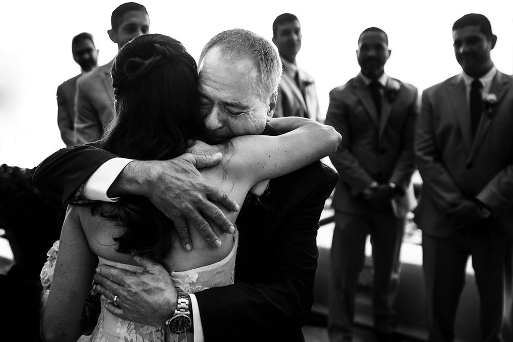 Dad of the bride hugs her daughter at the end of the aisle