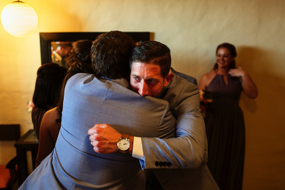 Groom hugs a groomsman after the ceremony while crying