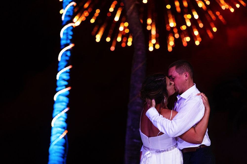 Bride and groom kiss on their first dance under fireworks