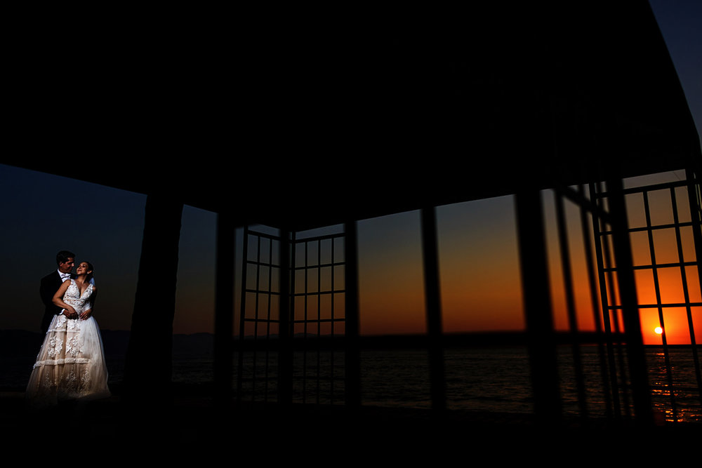 Bride and groom against the romantic mexican sunset with a game of silhouette geometry