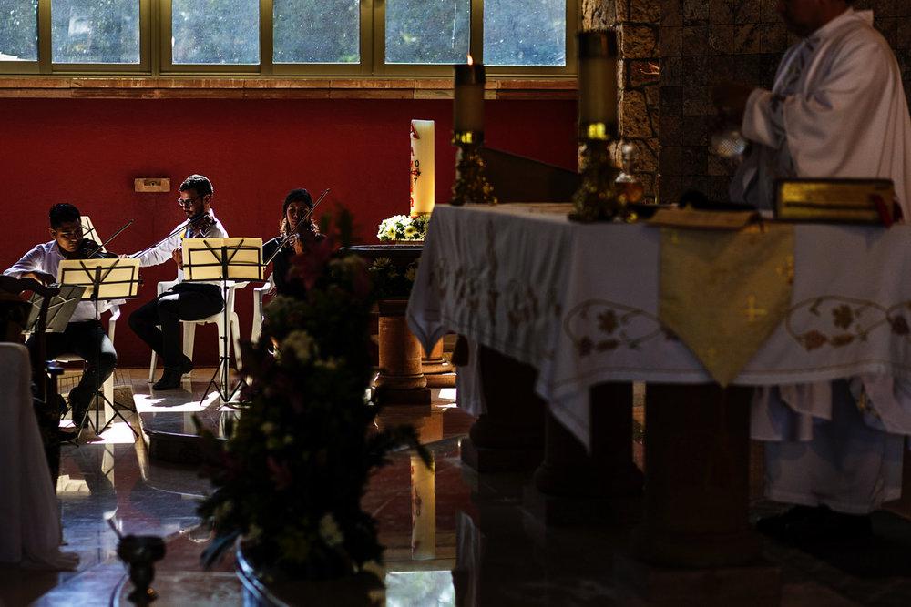 Strings trio plays during catholic wedding ceremony at church