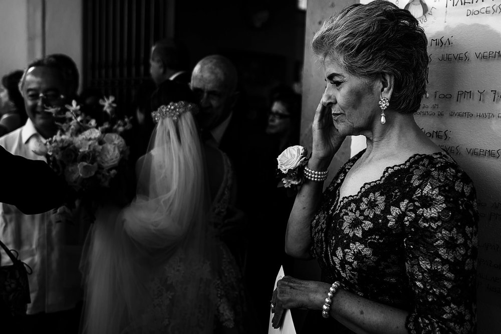Mother of the groom cries behind the bride that is being congratulated by wedding guests outside the church
