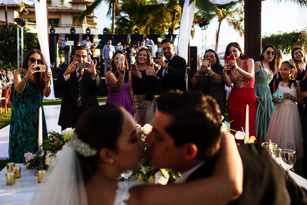 Wedding guests getting a snap photo with their phones of bride and groom about to kiss