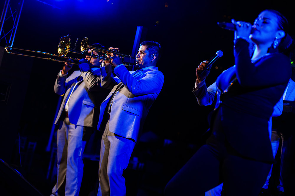 Brass section of he music band on stage with blue lights and female singer in the foreground