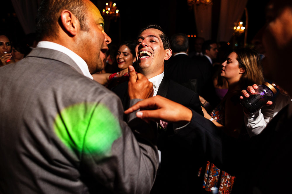 Groom jokes with friends at the wedding party and dancing