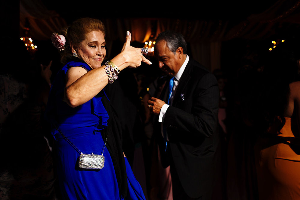 """well dress lady guests dancing as she throws a """"cholo"""" sign"""