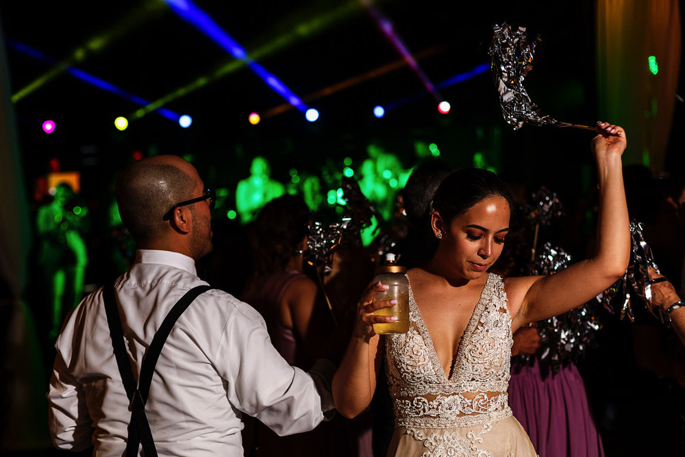 Bride dancing with brother-in-law holding a drink and waving a stick with silver feathers