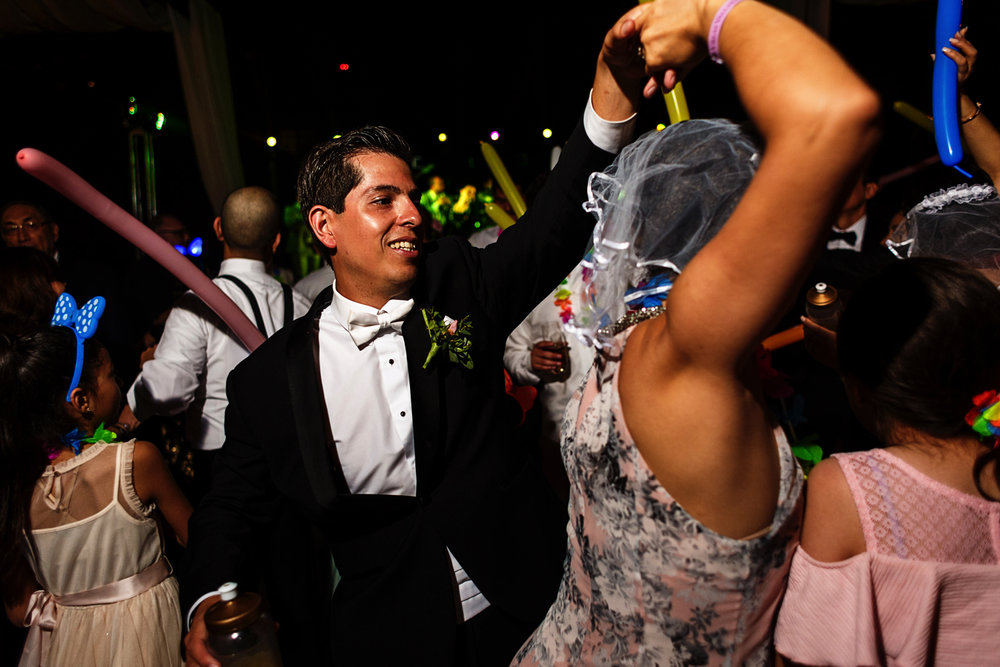 Groom spining and dancing with a wedding guest
