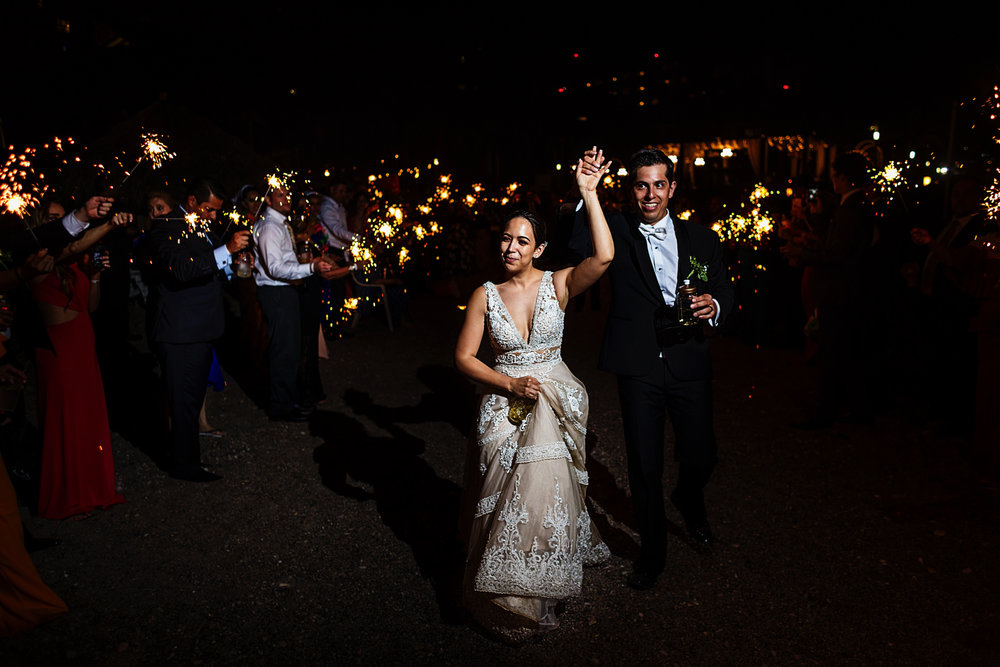 Bride and groom exit the wedding with sparklers on both sides of a friends corridor