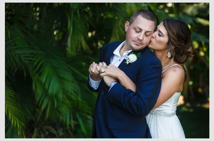 Bride hugs from behind the groom as she kiss him on the check against a wall of palm trees background