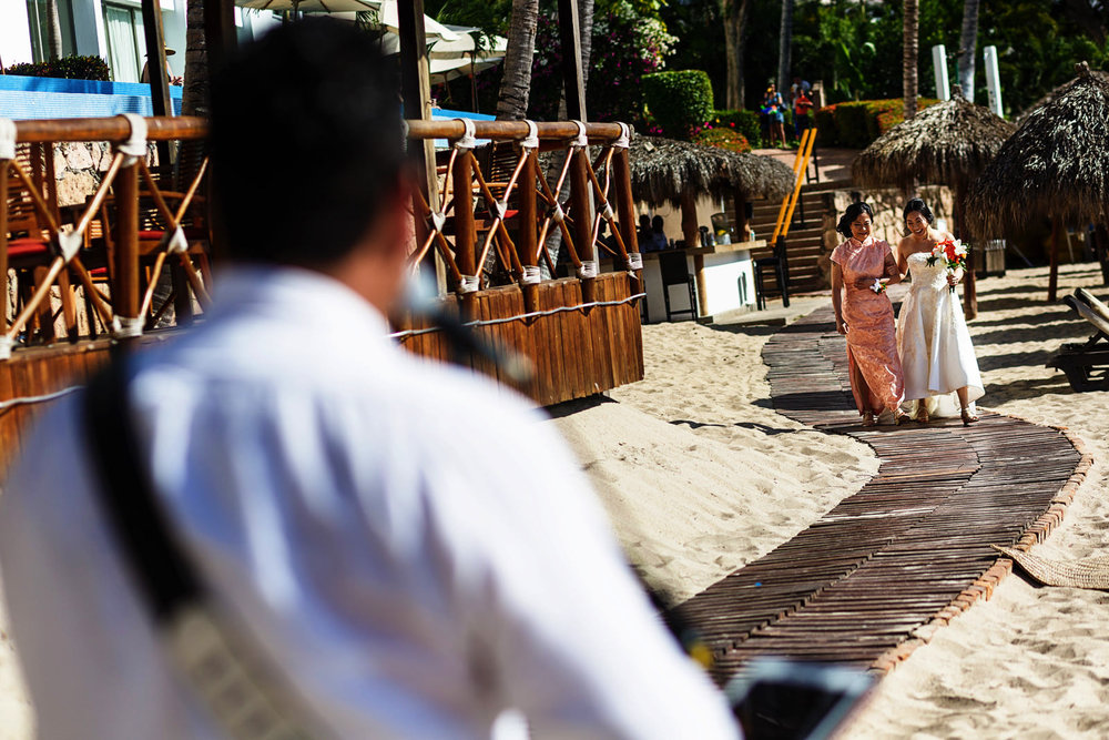 Bride and her mother walk on a wood-made path in the beach while a performer sings