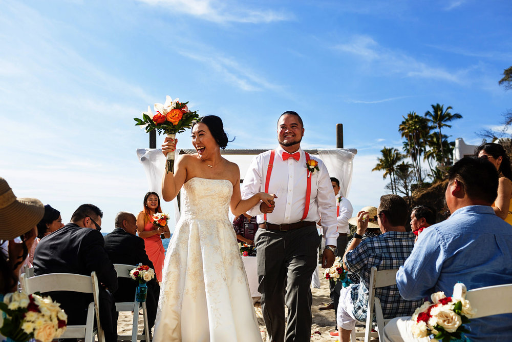 Bride and groom exit at the end of their wedding ceremony on the beach