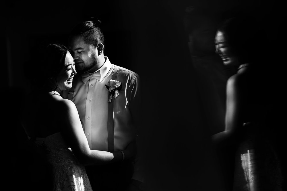 Groom and bride portrait in black and white on a spot of direct sunlight and a reflection of the bride's laugh