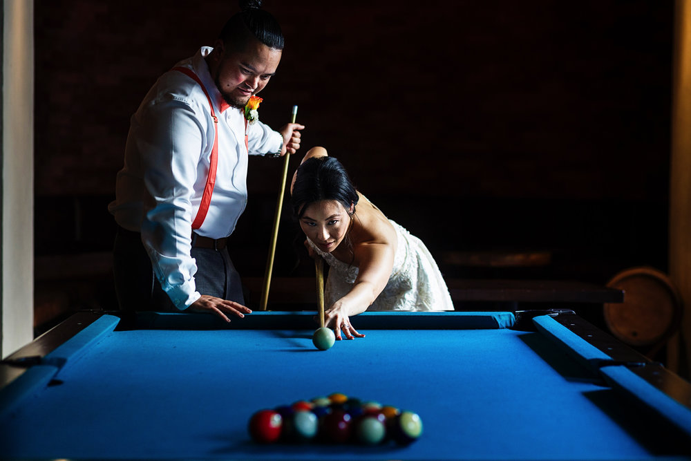 Bride and groom playing table pool