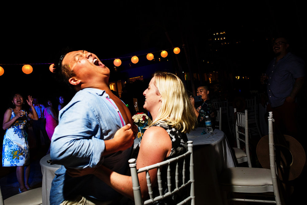 Wedding guest removes the upper part of the shirt as part of a lap dance to his wife