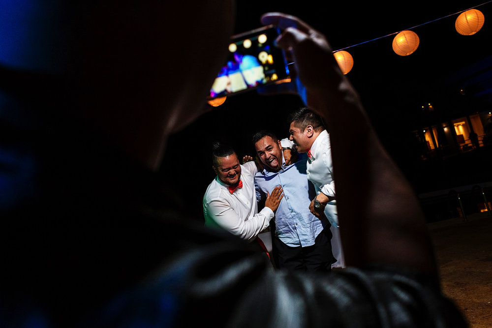 Wedding guests taking a video of the groom, best man and other guest having fun