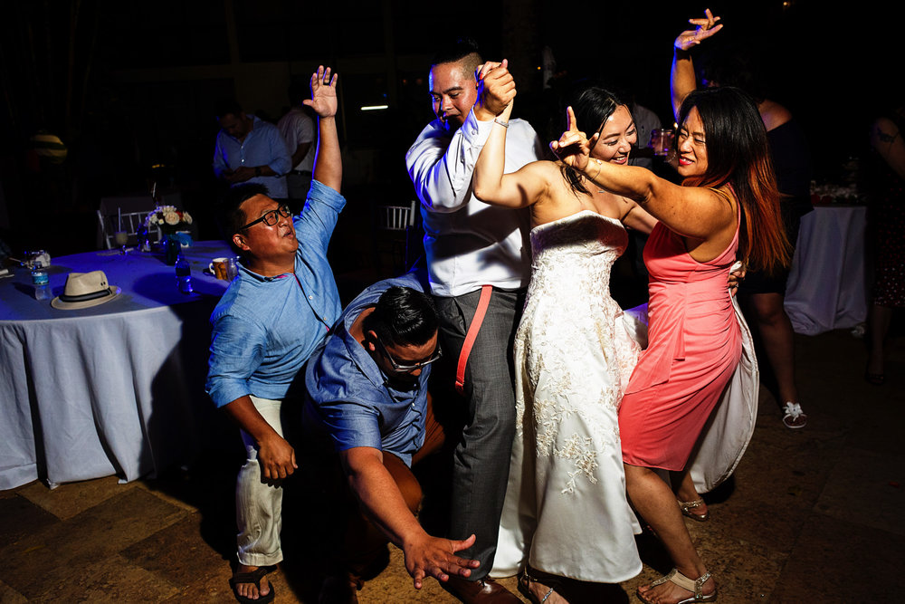Wedding guests do a sandwich dance with groom and bride in the middle