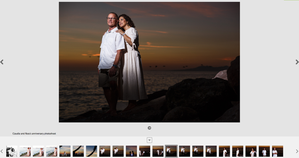 Married couple standing over the rock near the pacific ocean with the Mexican sunset in the background.