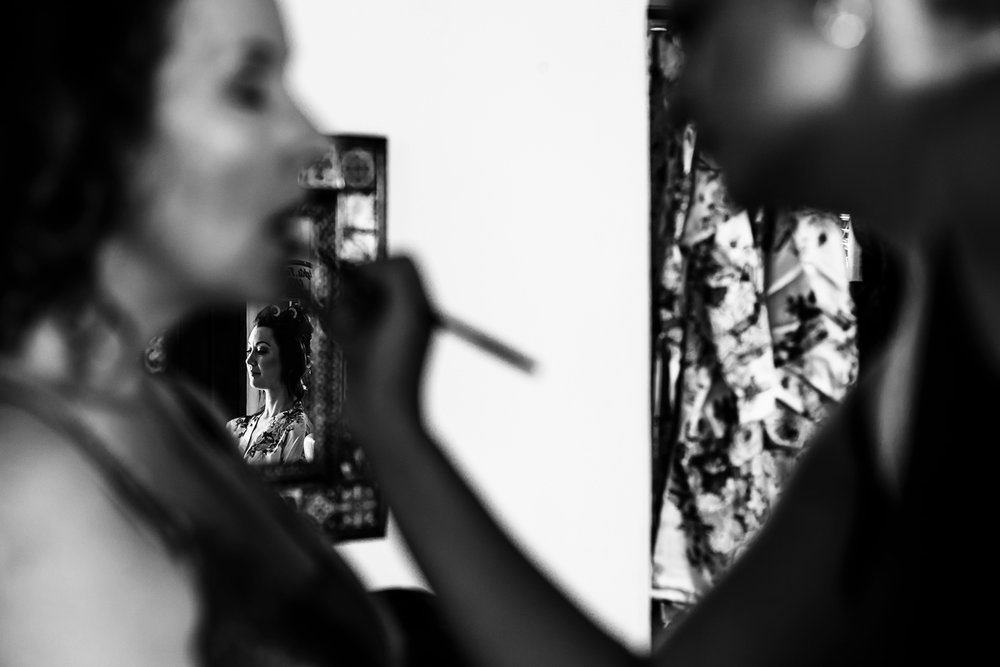 Bride reflection on a mirror through the mother make-up getting done