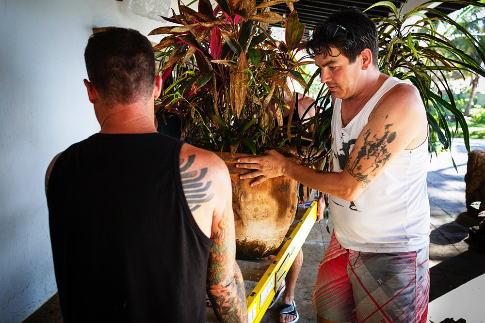 Groom helping move some plants and pots to arrange the ceremony space before the wedding